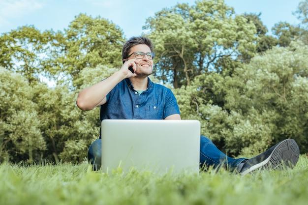 Giovane che per mezzo dello smartphone mentre sedendosi sull'erba