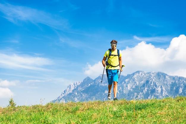 Giovane che pratica l'attività fisica montagna e che corre con i bastoni