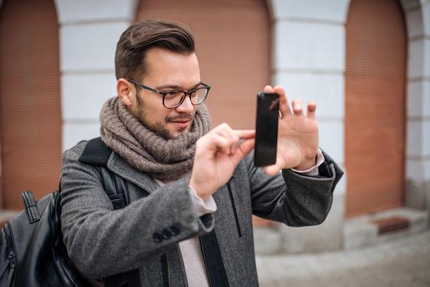 Giovane che prende foto sullo smart phone nella città il giorno di inverno.