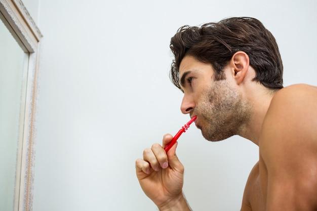 Giovane che pulisce i suoi denti in bagno