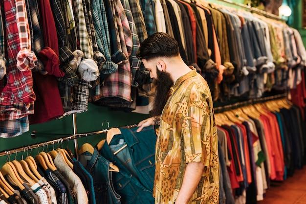 Giovane che sceglie i vestiti su una cremagliera in uno showroom
