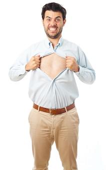 Giovane che si comporta come un super eroe e strappa la camicia su uno sfondo bianco