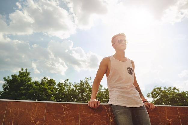 Giovane che si distende, godendo di una giornata di sole, mentre in piedi su un bui