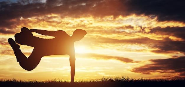 Giovane che si esercita, facendo acrobazie al tramonto.