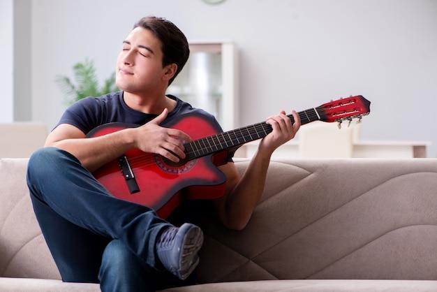 Giovane che si esercita nel suonare la chitarra a casa
