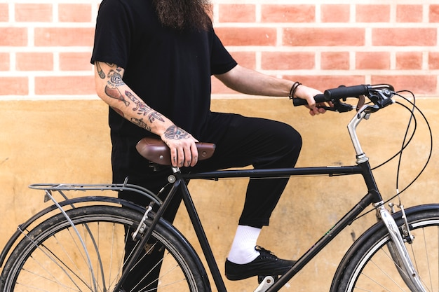 Giovane che si leva in piedi con la bicicletta contro la parete