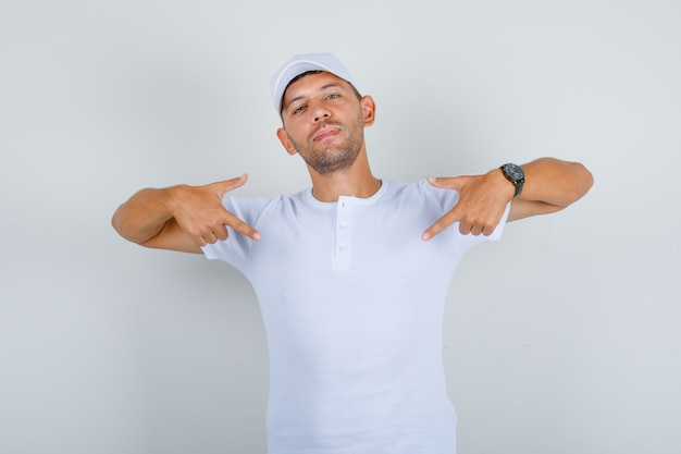 Giovane che si mostra con le dita indice in maglietta bianca, berretto e guardando fiducioso, vista frontale.