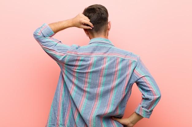 Giovane che si sente incapace e confuso, pensando a una soluzione, con la mano sull'anca e l'altro sulla testa, vista posteriore su sfondo rosa