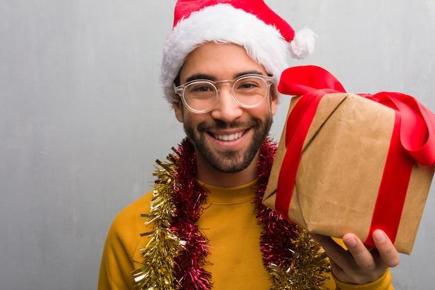 Giovane che si siede con i regali che celebrano il natale allegro con un grande sorriso