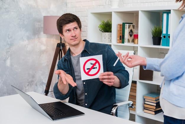 Giovane che si siede nell'ufficio che mostra segno non fumatori alla sigaretta della tenuta della donna
