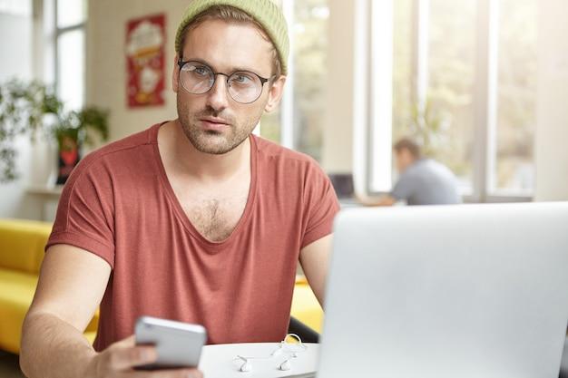 Giovane che si siede nella caffetteria con il computer portatile