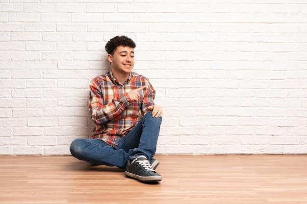 Giovane che si siede sul pavimento che indica il lato per presentare un prodotto