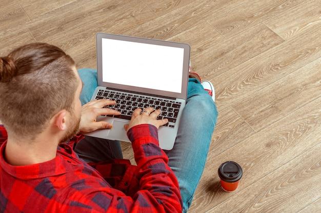 Giovane che si siede sul pavimento con il computer portatile