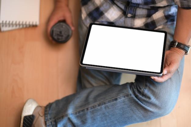 Giovane che si siede sul pavimento con il lavoro sul tablet