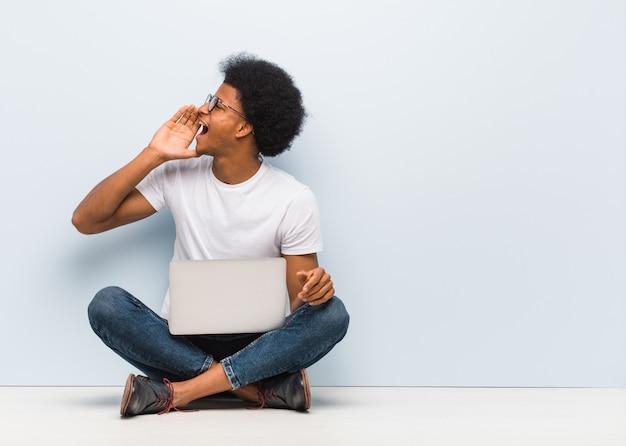 Giovane che si siede sul pavimento con un computer portatile che bisbiglia sottotono di gossip