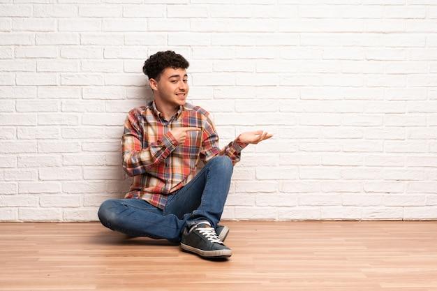 Giovane che si siede sul pavimento tenendo copyspace immaginario sul palmo per inserire un annuncio