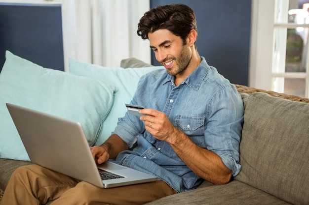 Giovane che si siede sul sofà e che compera online sul computer portatile