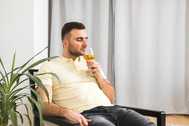 Giovane che si siede sulla sedia che odora la bevanda in bicchiere di vino