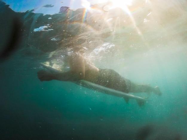 Giovane che si trova sulla tavola da surf in acqua blu