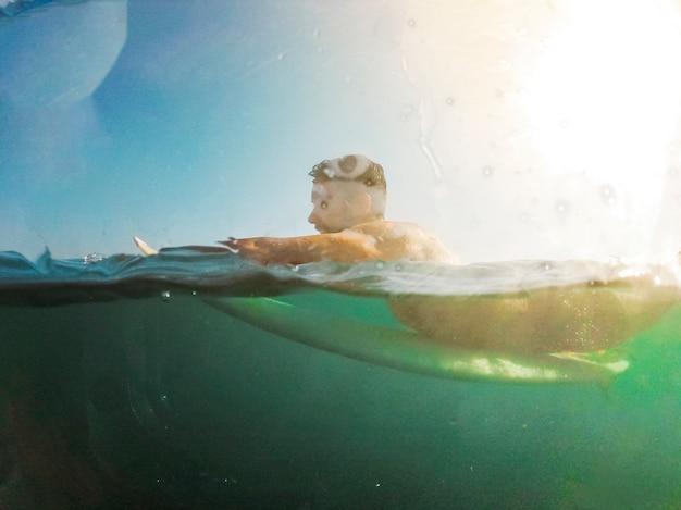 Giovane che si trova sulla tavola da surf in acqua