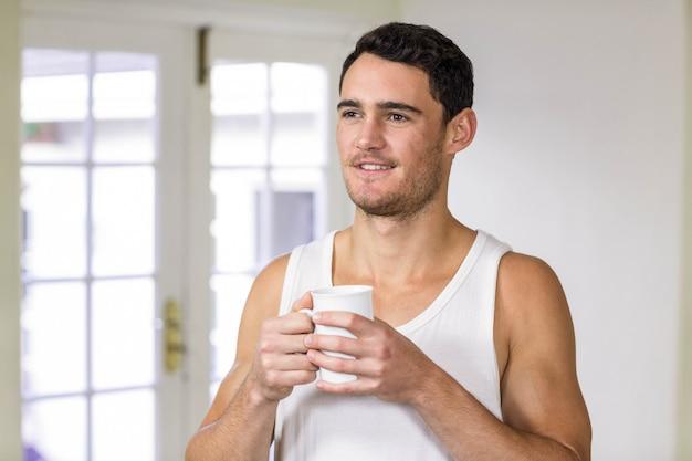 Giovane che sorride e che tiene una tazza di tè in cucina