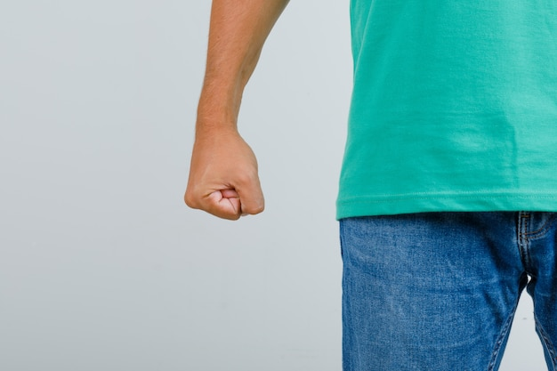 Giovane che sta con il pugno chiuso in maglietta verde, jeans e che sembra arrabbiato, vista frontale.