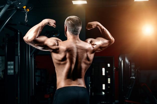 Giovane che sta forte nella palestra e che flette i muscoli