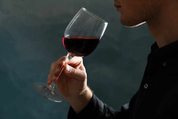 Giovane che tiene il vetro del vino rosso contro il fondo scuro, spazio per testo