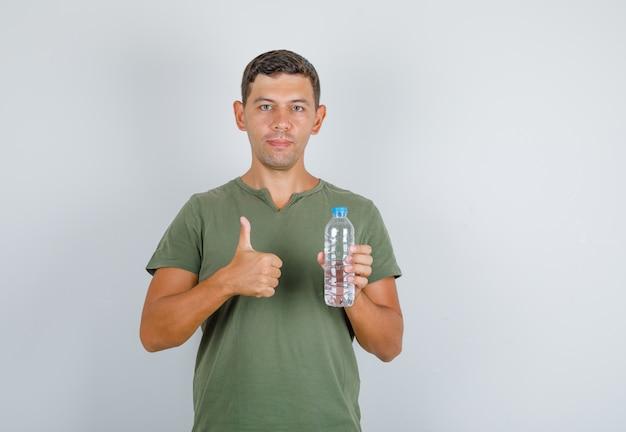 Giovane che tiene la bottiglia di acqua e che mostra il pollice in su nella vista frontale della maglietta verde dell'esercito.