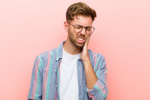 Giovane che tiene la guancia e che soffre di mal di denti doloroso, sentirsi male, miserabile e infelice, in cerca di un dentista contro il muro rosa