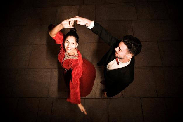 Giovane che tiene la mano di ballare affascinante donna felice