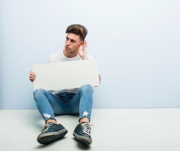 Giovane che tiene un cartello che si siede sul suo pavimento domestico che prova ad ascoltare un gossip.