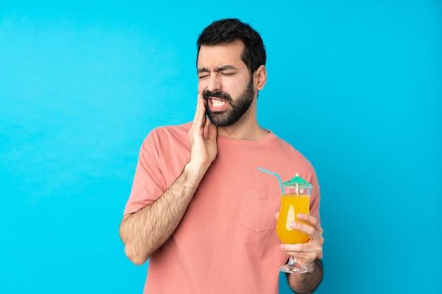 Giovane che tiene un cocktail con mal di denti
