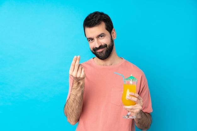 Giovane che tiene un cocktail sopra la parete blu isolata che fa gesto dei soldi