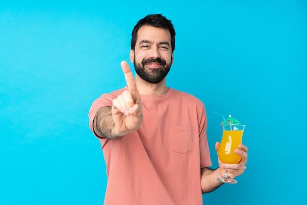Giovane che tiene un cocktail sopra la parete blu isolata che mostra e che solleva un dito