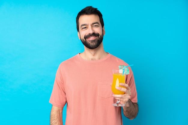 Giovane che tiene un cocktail sopra la risata blu isolata della parete