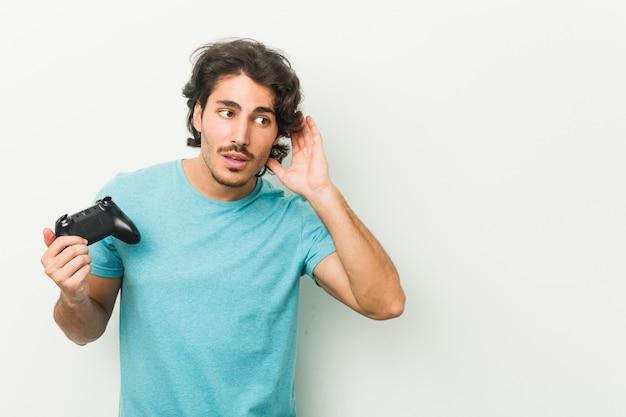 Giovane che tiene un controller di gioco che prova ad ascoltare un gossip.