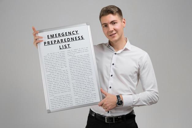 Giovane che tiene un elenco di preparazione di emergenza isolato su uno sfondo chiaro