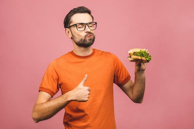 Giovane che tiene un pezzo di hamburger. lo studente mangia fast food. ragazzo molto affamato. pollice su.