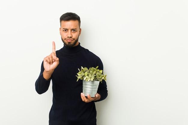 Giovane che tiene una pianta che mostra numero uno con il dito.
