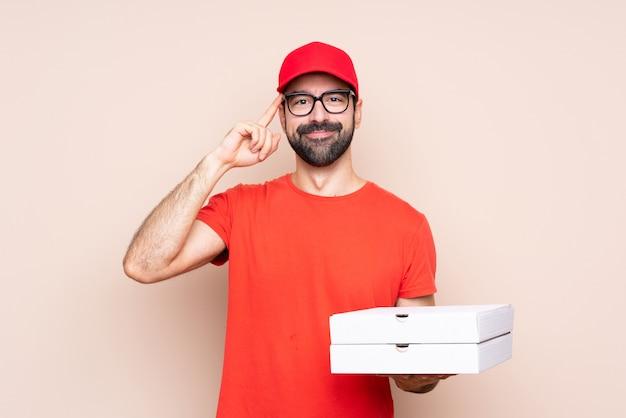 Giovane che tiene una pizza sopra fondo isolato con i vetri e felice