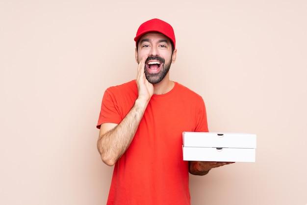 Giovane che tiene una pizza sopra gridare isolato e annunciare qualcosa