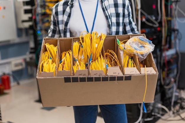 Giovane che tiene una scatola con diversa fibra ottica