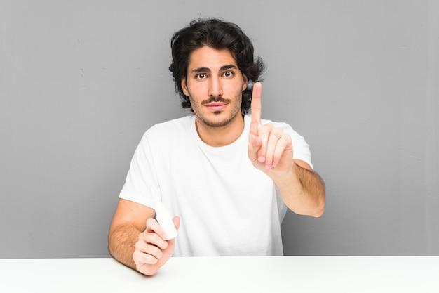 Giovane che tiene uno spray nasale mostrando il numero uno con il dito.