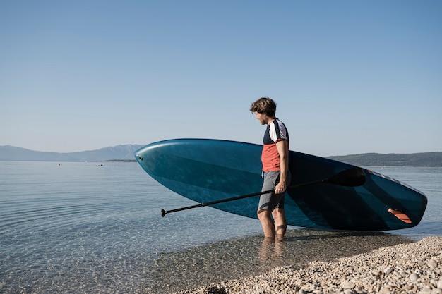 Giovane che trasporta il suo stand up paddle board nell'acqua di mare calmo