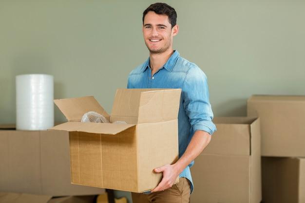 Giovane che trasportano scatole di cartone nella sua nuova casa