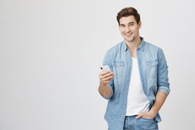 Giovane che utilizza il telefono cellulare, messaggistica con un amico