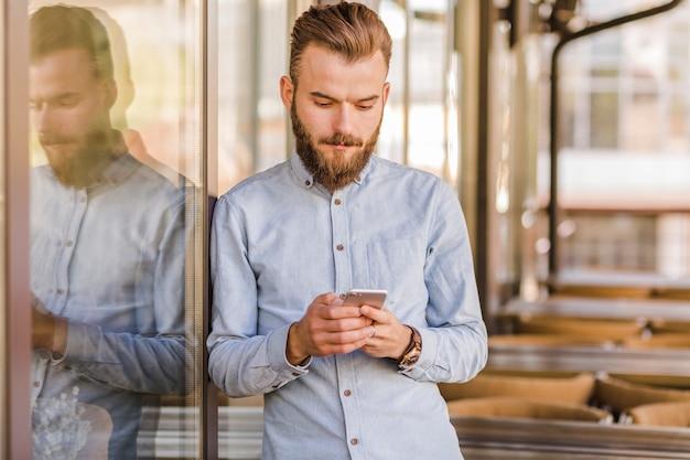 Giovane che utilizza smartphone nel ristorante