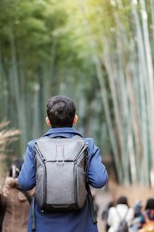 Giovane che viaggia al boschetto di bambù di arashiyama, viaggiatore asiatico felice che guarda la foresta di bambù di sagano. punto di riferimento e popolare per le attrazioni turistiche di kyoto, in giappone. concetto di viaggio in asia