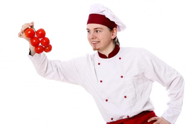 Giovane chef con pomodori